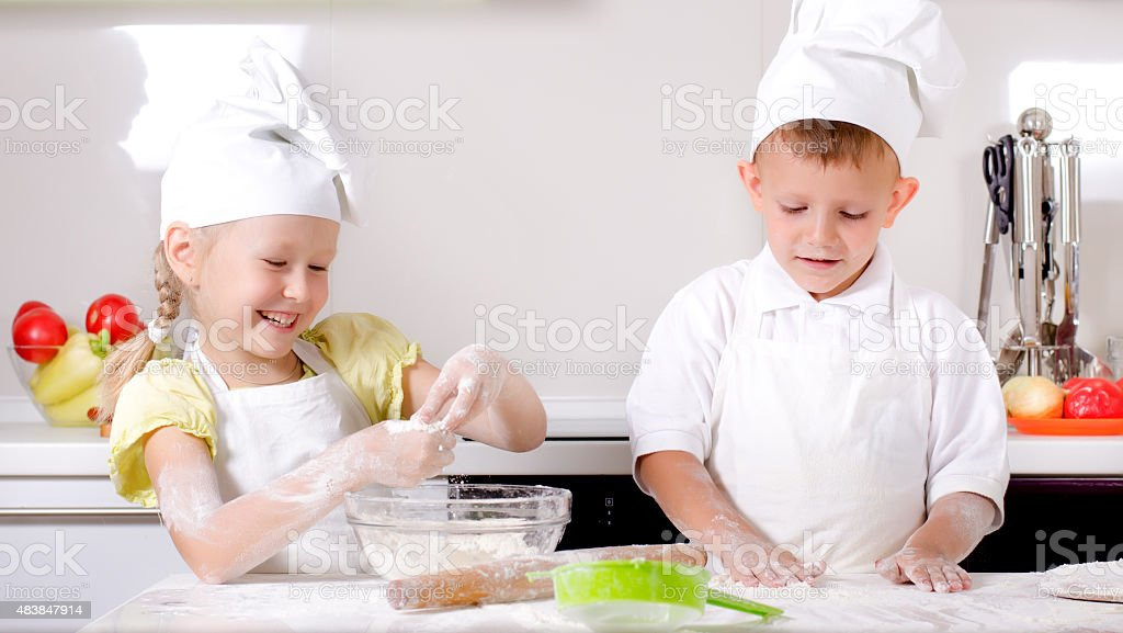 Happy little boy and girl cooking in the kitchen stock photo