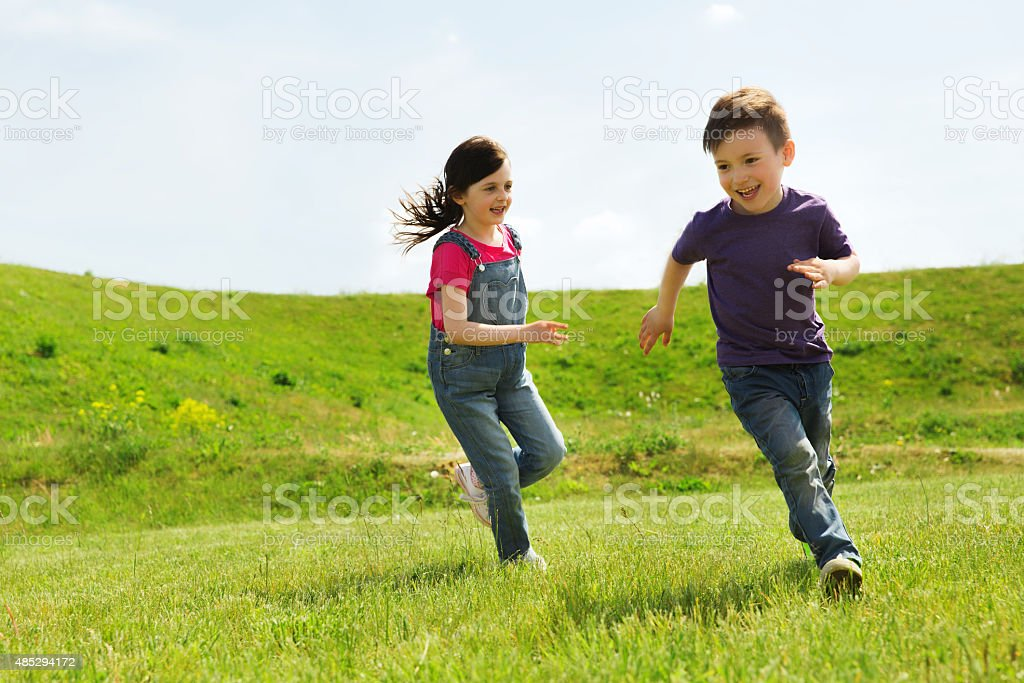 happy little boy and girl running outdoors stock photo