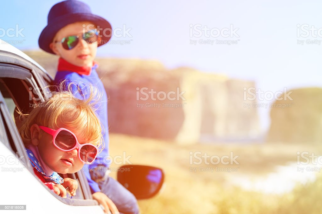 happy little boy and girl travel by car in mountains stock photo