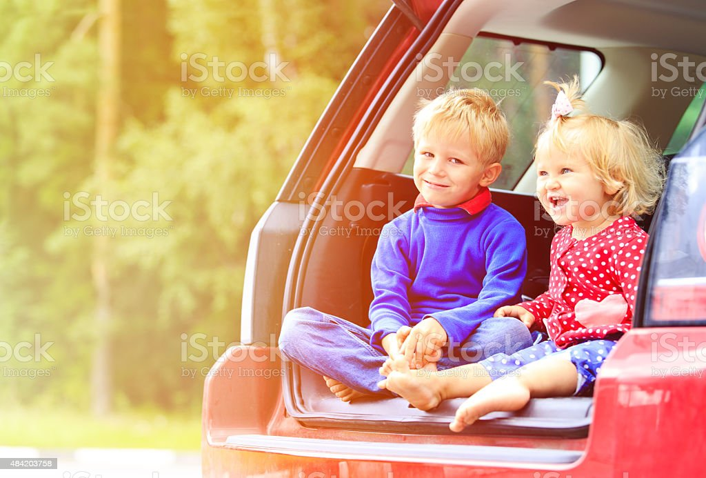 happy little boy and girl travel by car stock photo