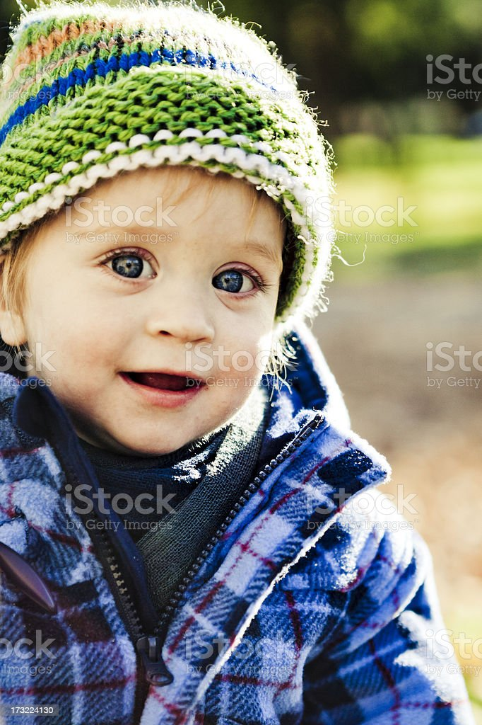 Happy little boy dressed in plaid shirt and green knit hat royalty-free stock photo