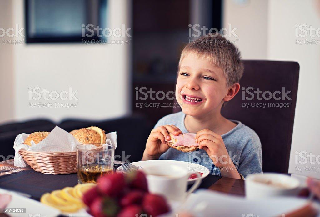 Happy little boy eating breakfast stock photo
