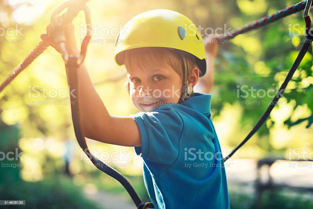 Happy little boy enjoying ropes course adventure park stock photo