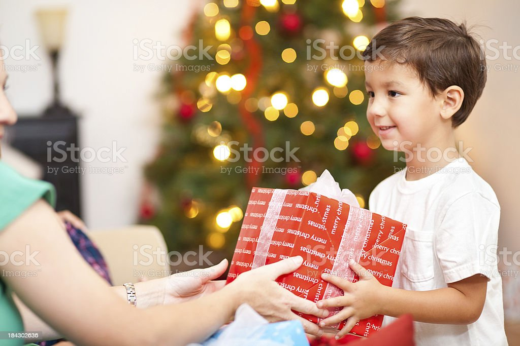 Happy Little Boy Giving Present To Mother on Christmas Morning royalty-free stock photo
