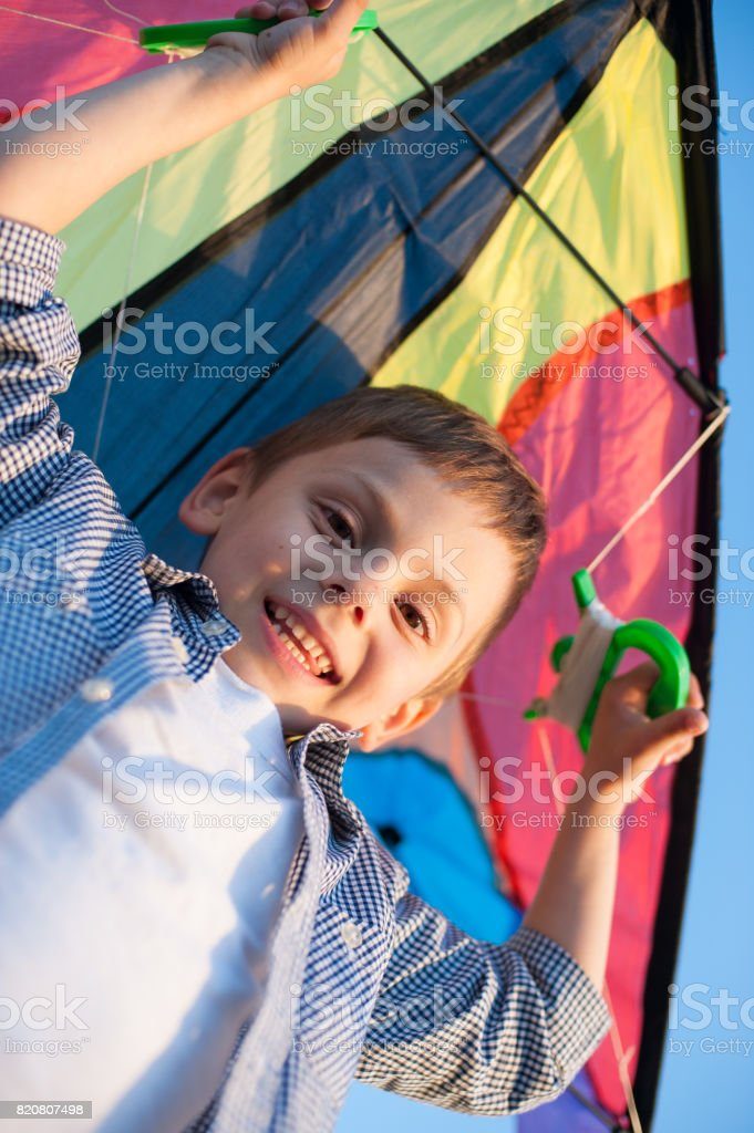 happy little boy holding kite over his head and looking into the camera stock photo