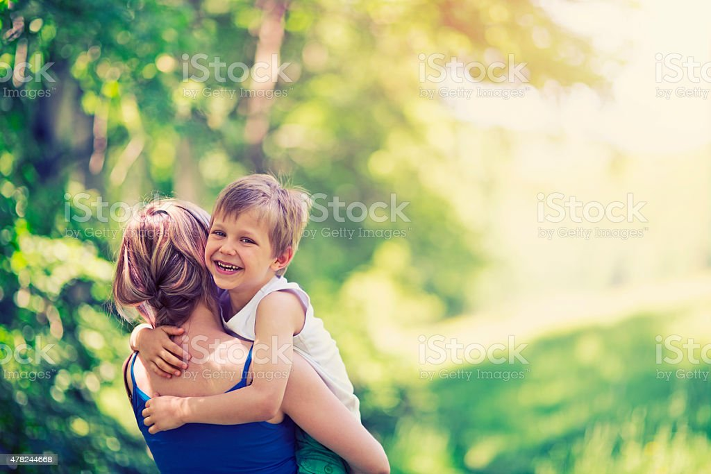 Happy little boy hugging his mother in forest stock photo