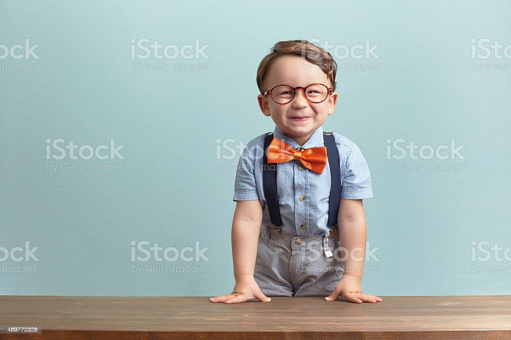 Happy little boy in an orange bow tie and glasses stock photo