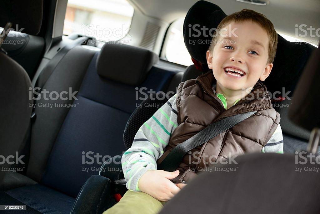 Happy little boy in car safety seat. stock photo