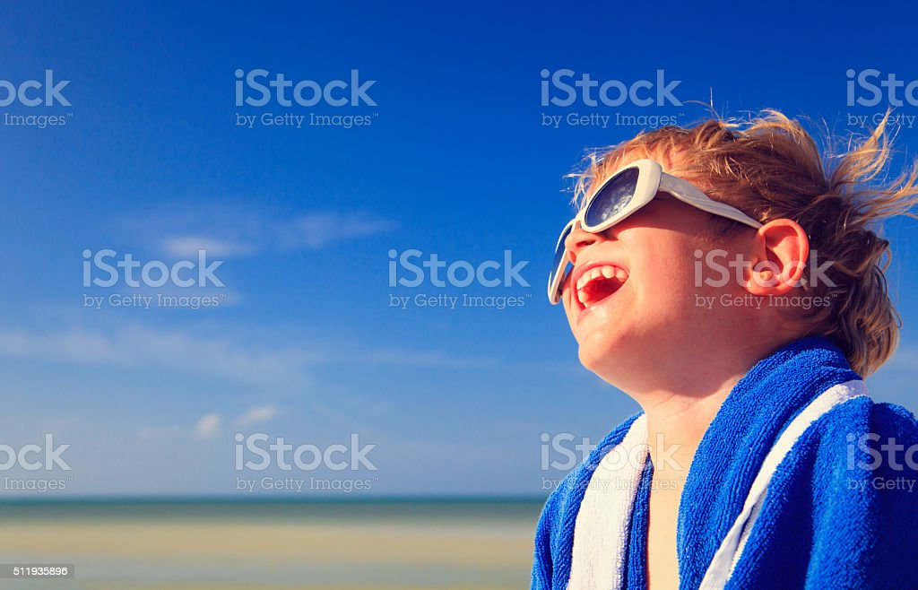 happy little boy laugh wrapped in beach towel stock photo