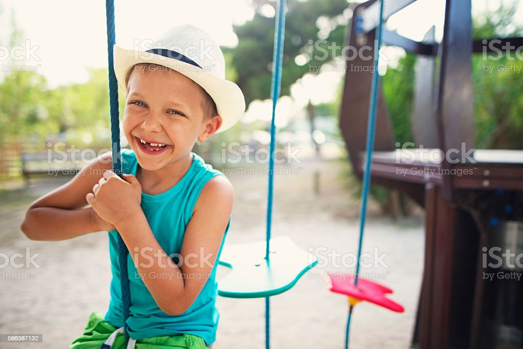 Happy little boy laughing at the playground stock photo