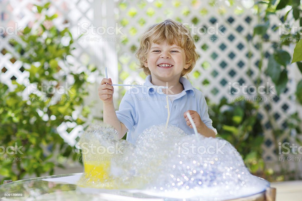 Happy little boy making experiment with colorful water and soap stock photo