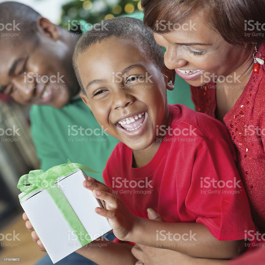 Happy little boy opening Christmas present with parents royalty-free stock photo