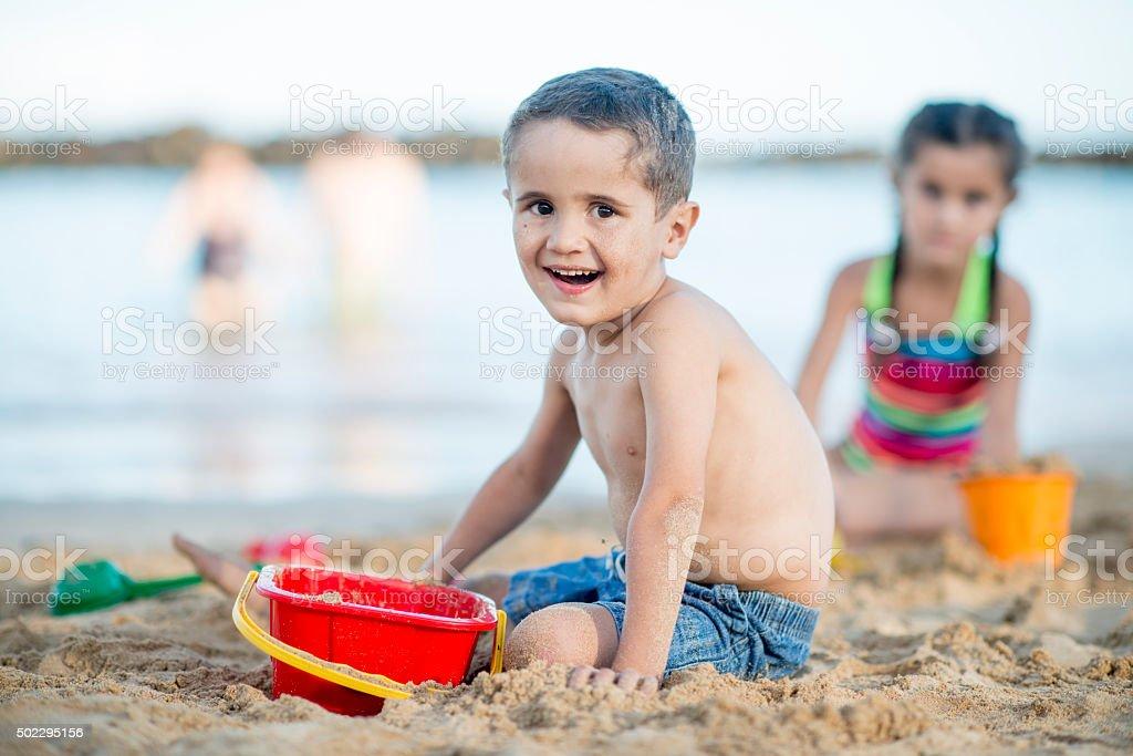 Happy Little Boy Playing on a Sandy Beach stock photo