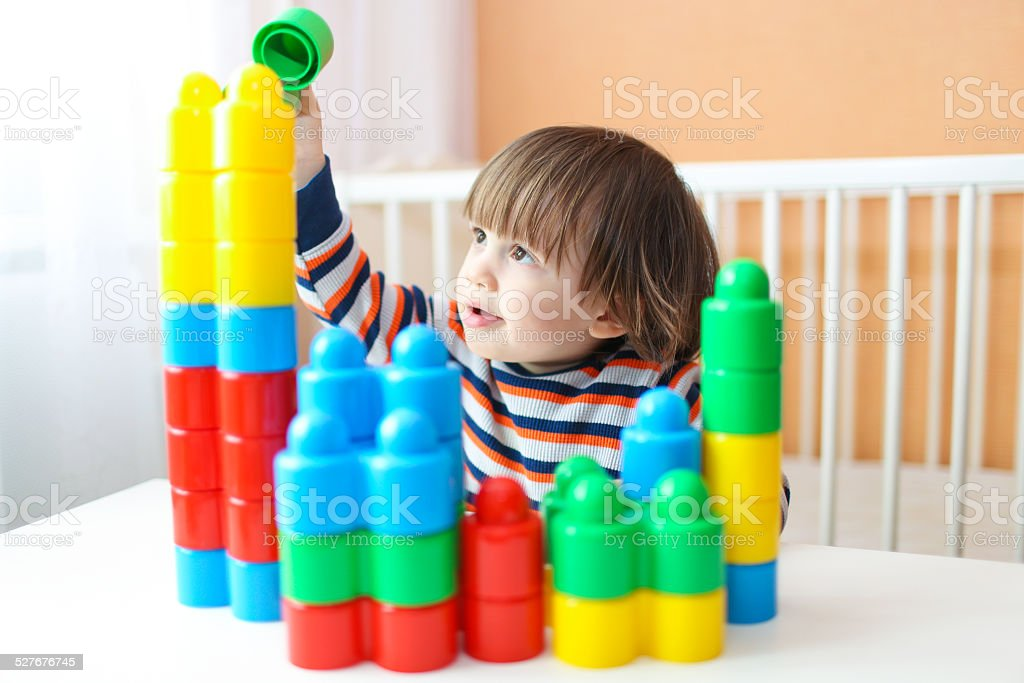 happy little boy playing plastic blocks stock photo