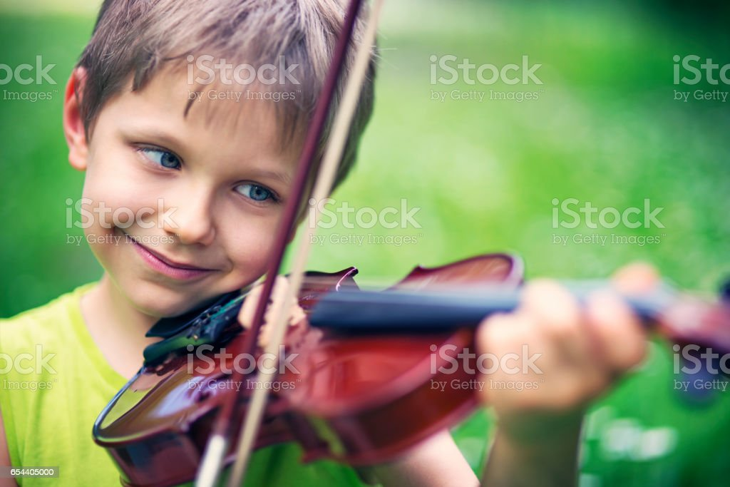 Happy little boy playing violin on spring grass field stock photo