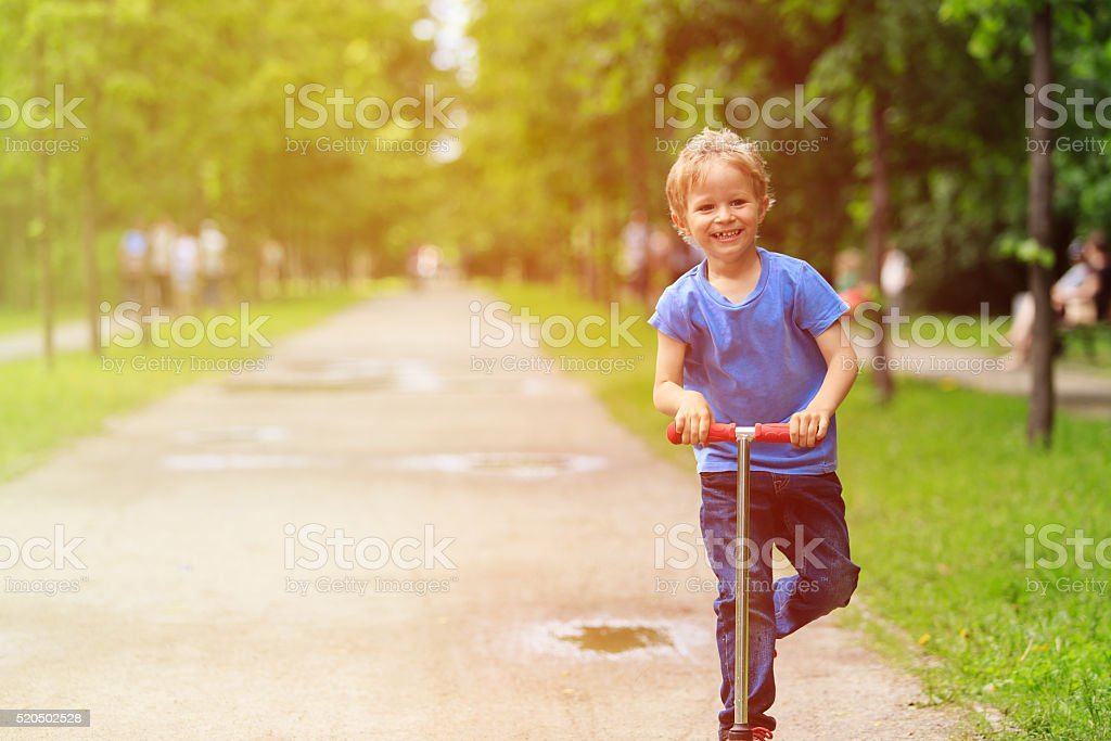 happy little boy riding scooter in summer stock photo