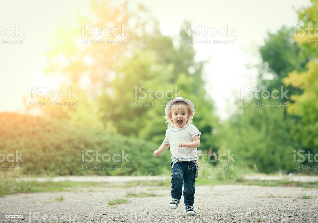 Happy little boy running and having fun stock photo