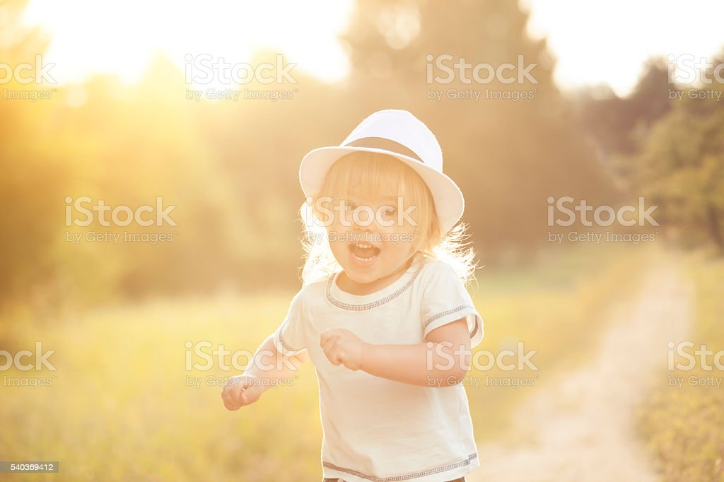 Happy little boy running in a park stock photo