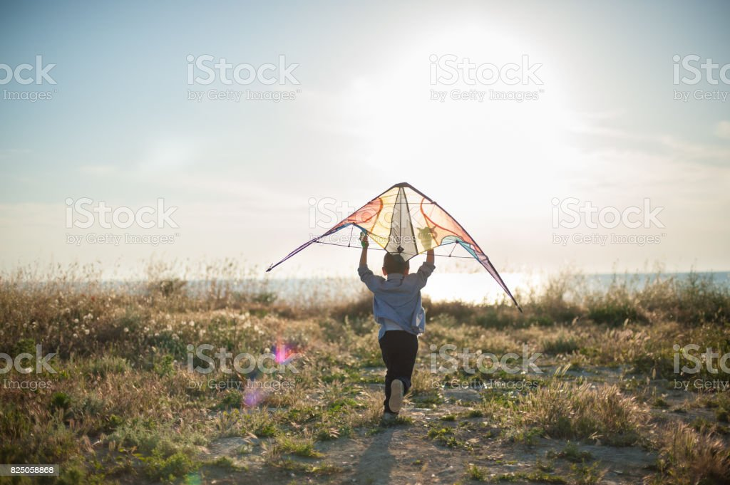 happy little boy running with a kite in his hands over his head stock photo