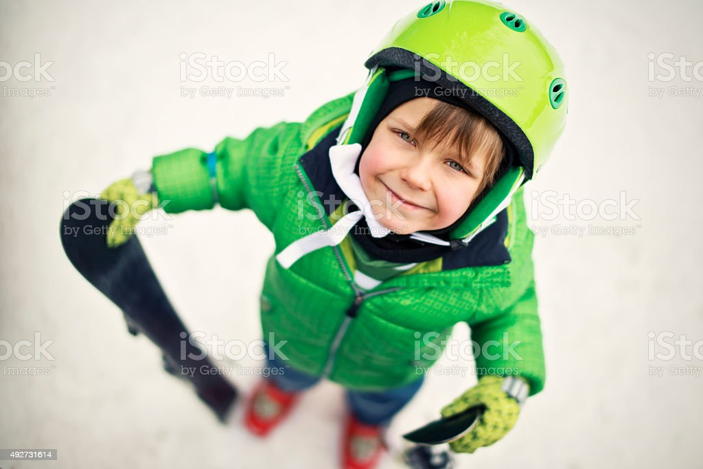 Happy little boy skiing stock photo