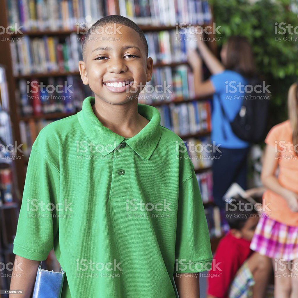 Happy little boy student in school library smiling stock photo