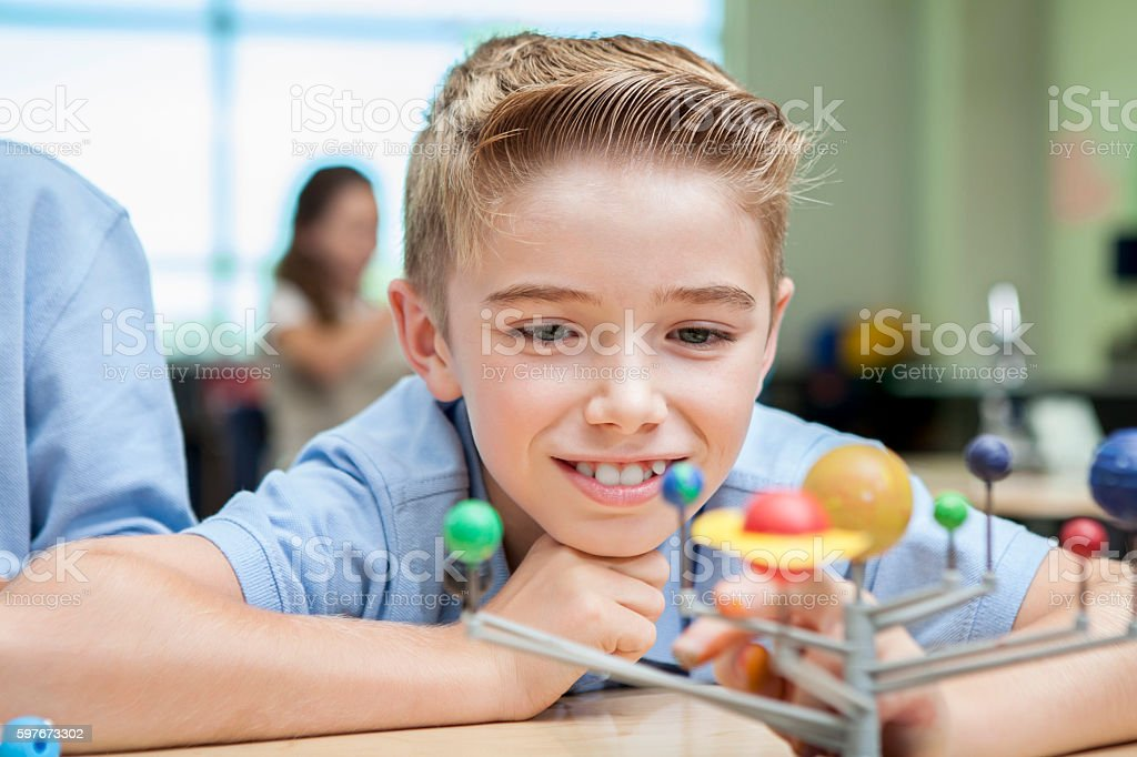 Happy little boy studying solar system model in classroom stock photo