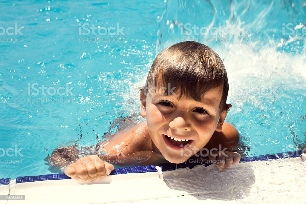 happy little boy swimming in the pool stock photo