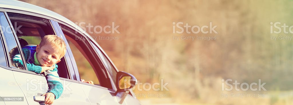 happy little boy travel by car in nature stock photo