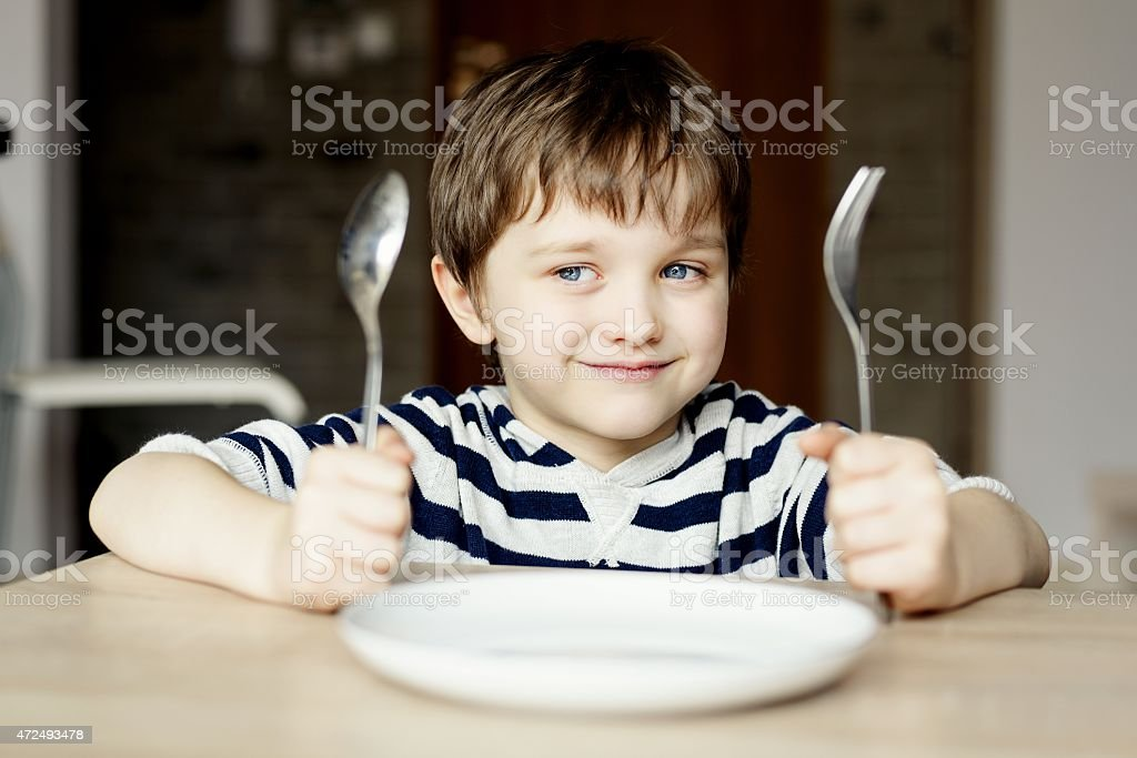 Happy little boy waiting for dinner. stock photo