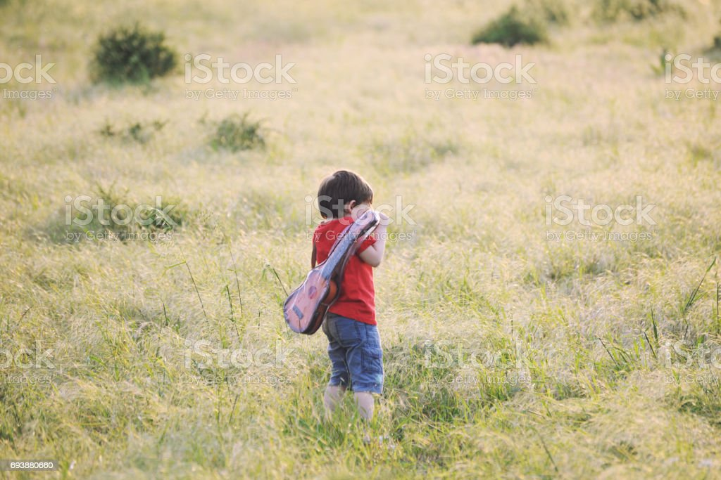 Happy little boy with a guitar on a meadow at sunset stock photo