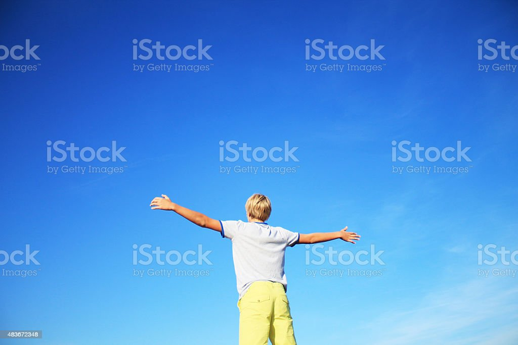 Happy little boy with arms raised up clear blue sky stock photo