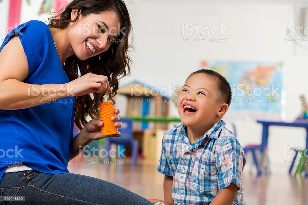 Happy little boy with Down Syndrome playing with bubbles stock photo