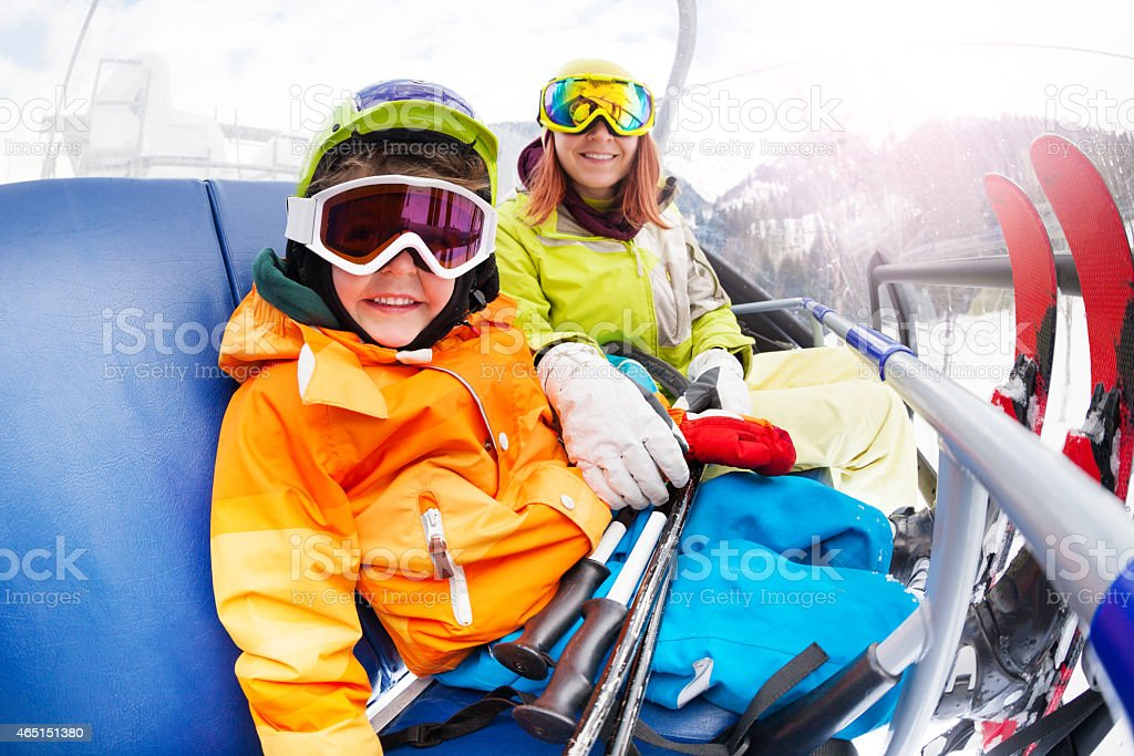 Happy little boy with mom, mountain ski chair lift stock photo