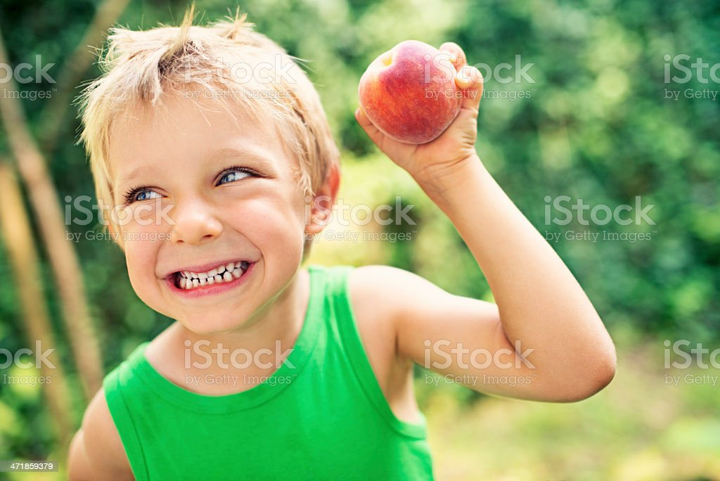 Happy little boy with peach royalty-free stock photo