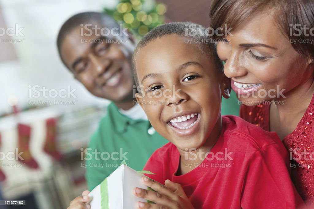 Happy little boy with present and family on Christmas morning royalty-free stock photo
