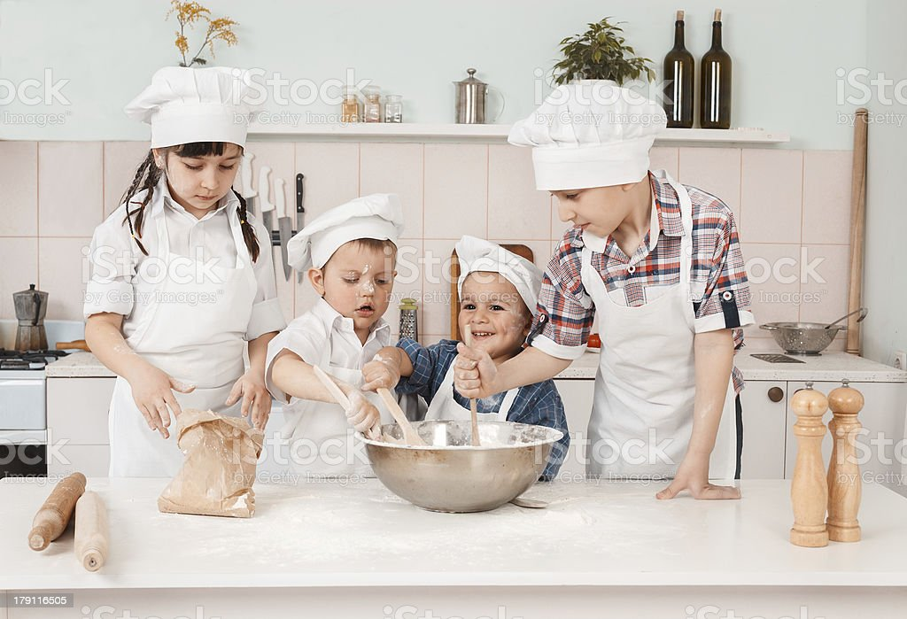 happy little chefs preparing dough in the kitchen royalty-free stock photo