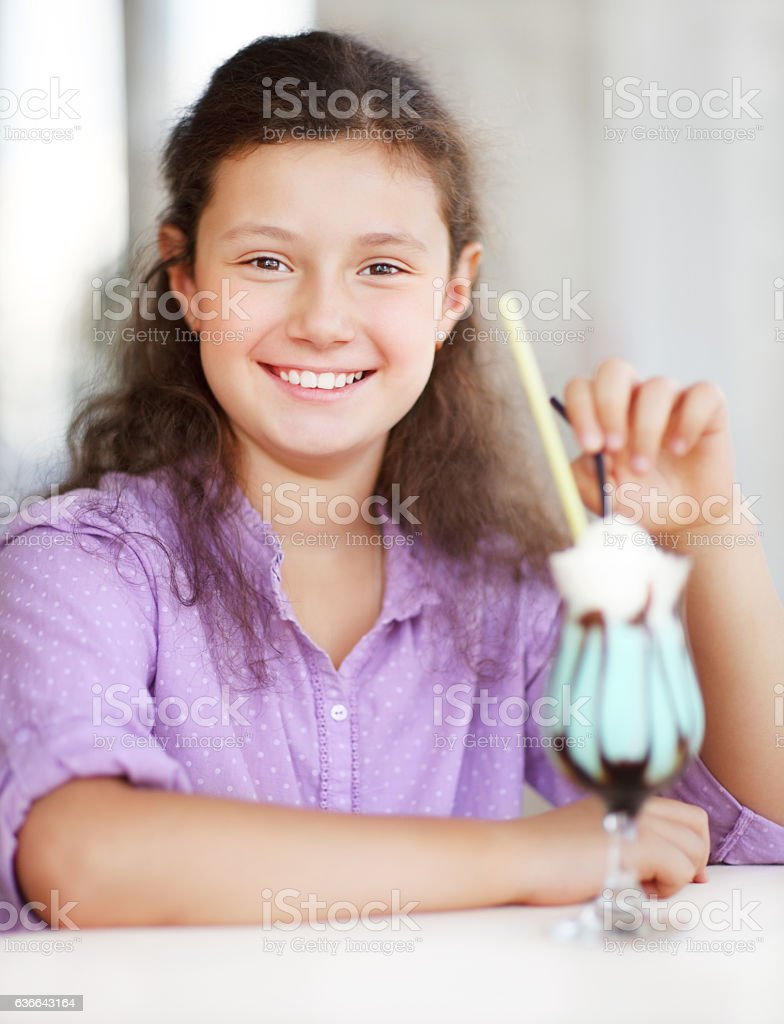 Happy little cute girl drinking shake stock photo
