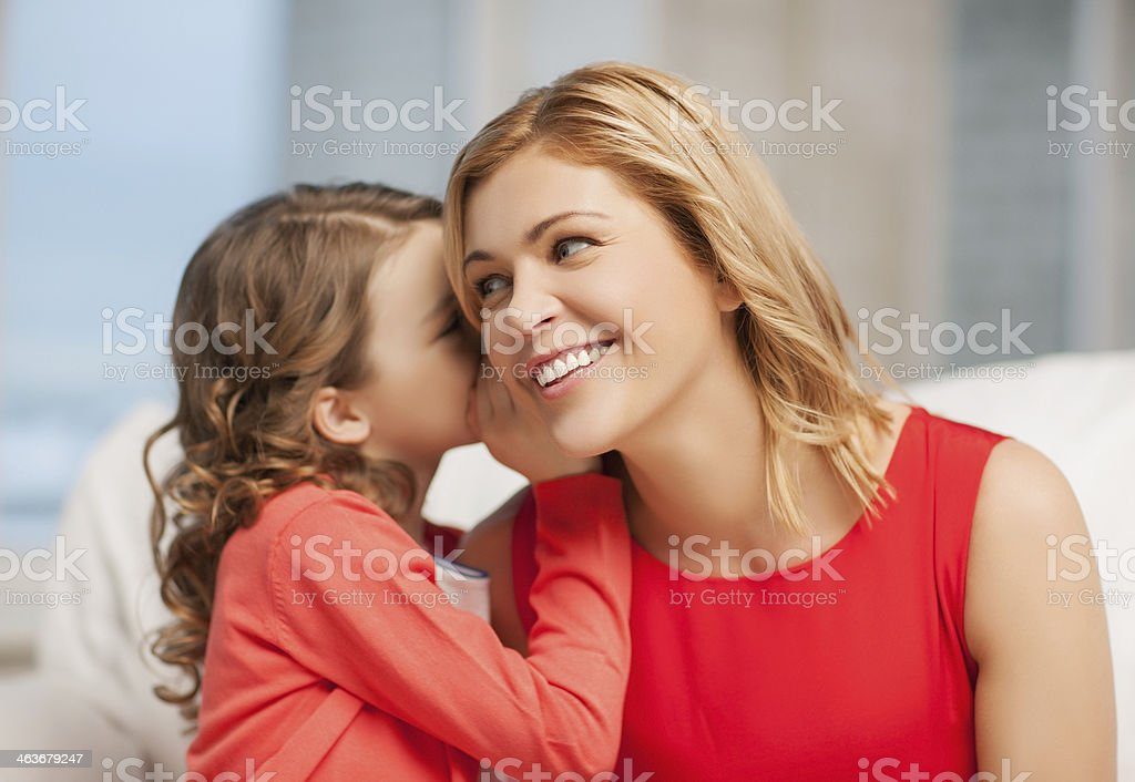 happy little daughter whispering to mother stock photo