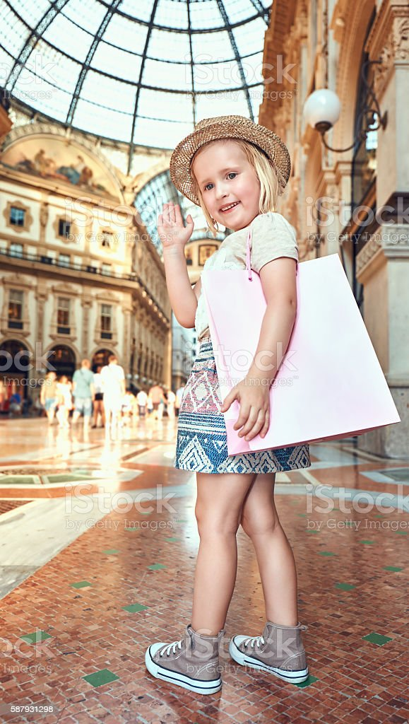 Happy little fashion monger with pink shopping bag hand waving stock photo