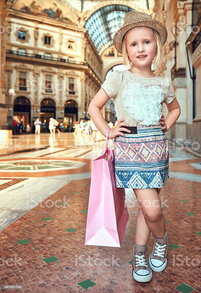Happy little fashion monger with pink shopping bag in Galleria stock photo