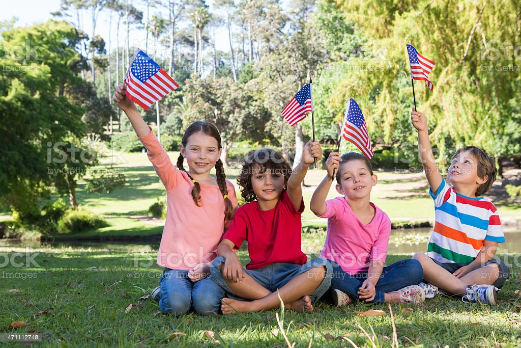 Happy little friends waving american flag stock photo