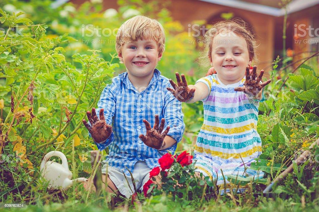 Happy little girl and boy in garden stock photo