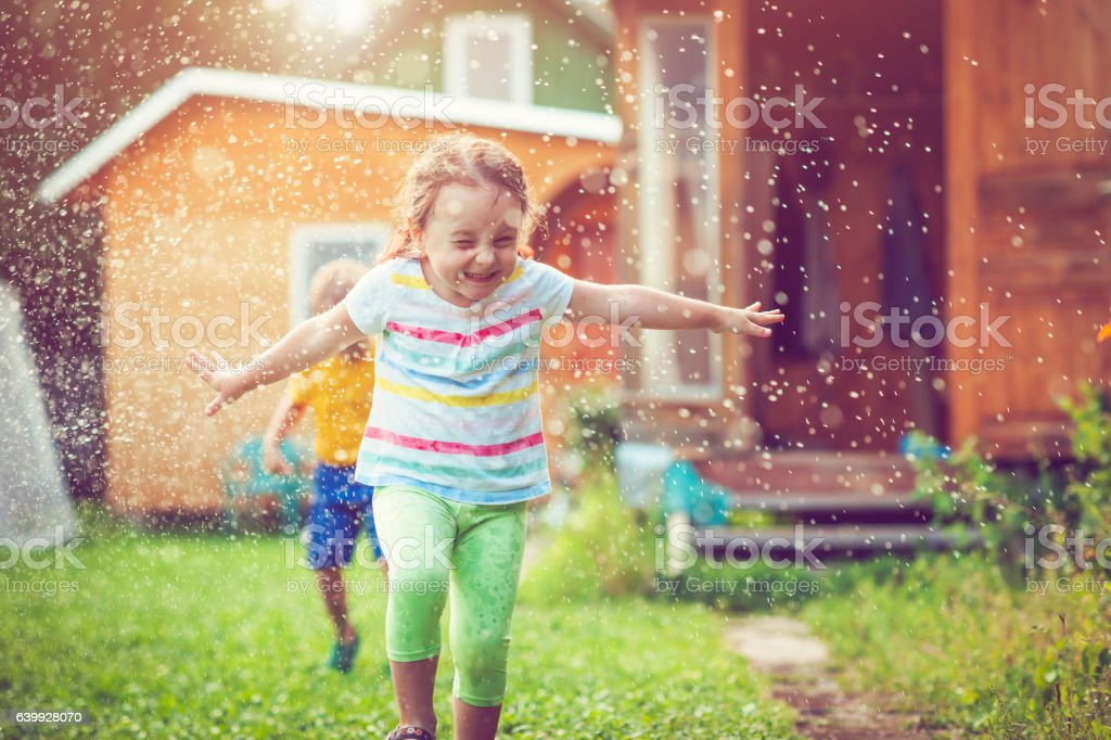 Happy little girl and boy playing with garden sprinkler stock photo