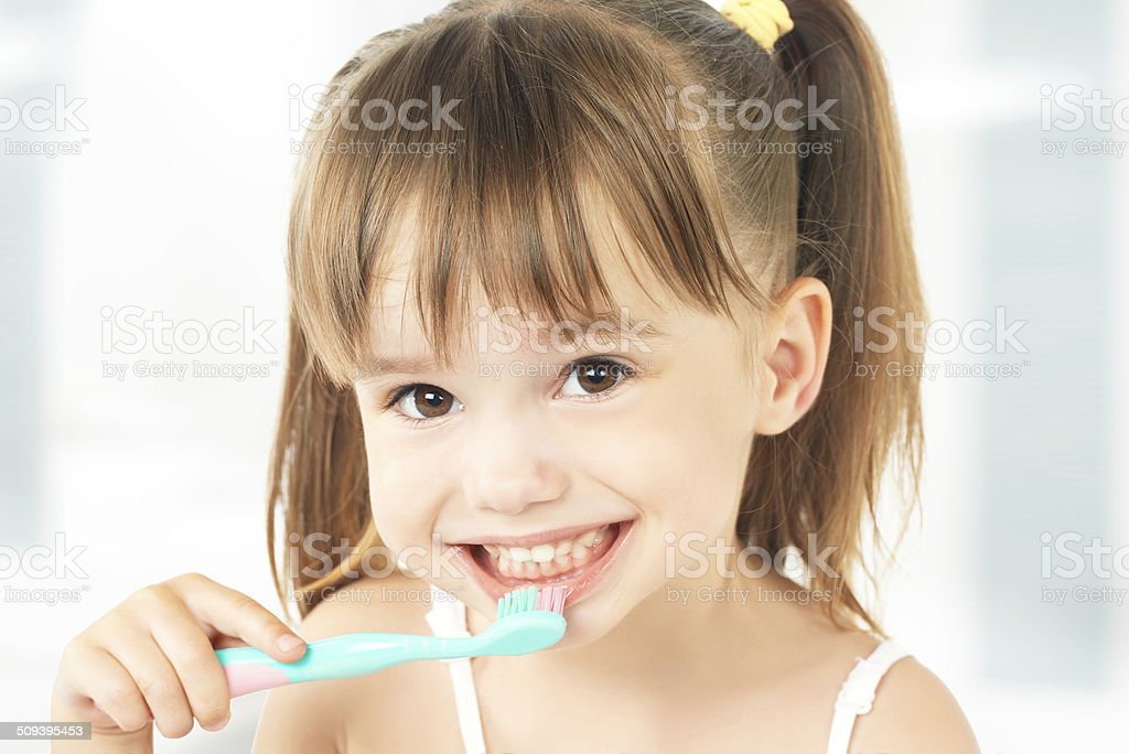 happy little girl brushing her teeth stock photo