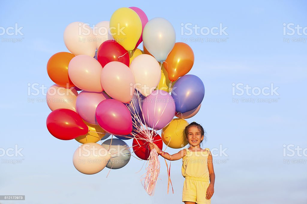 Happy little girl child kid with balloons on sky background stock photo