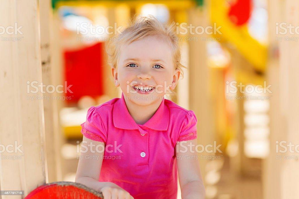 happy little girl climbing on children playground stock photo