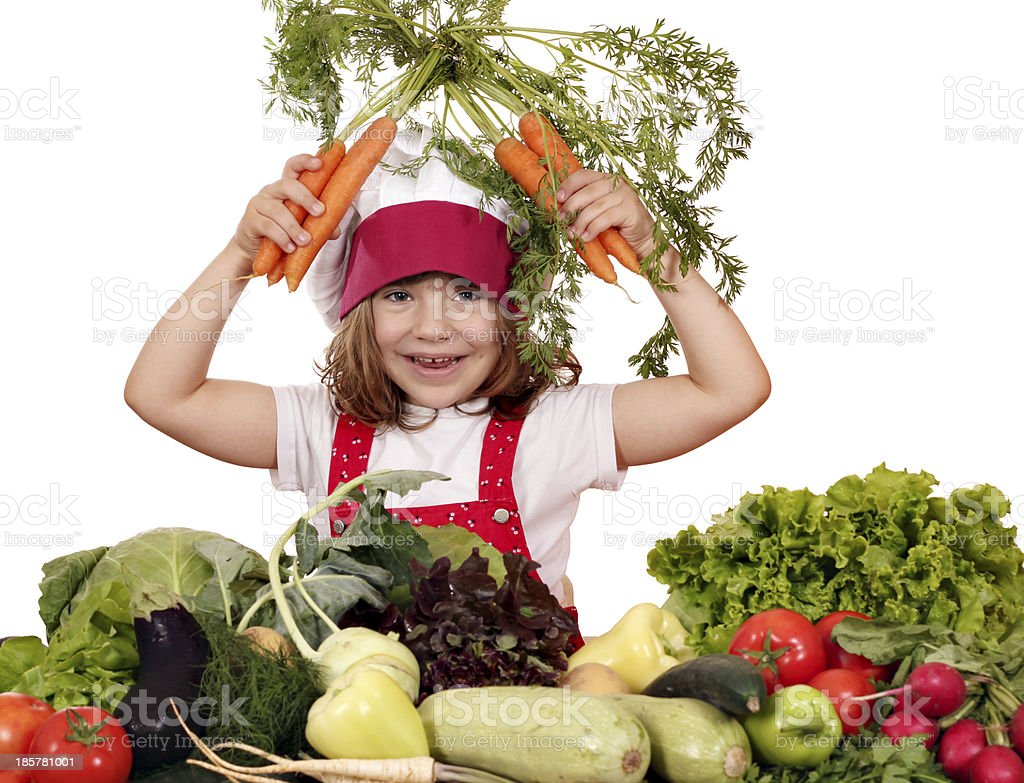 happy little girl cook with carrots and vegetables royalty-free stock photo