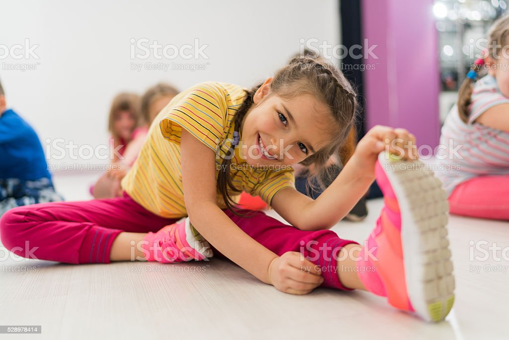 Happy little girl doing stretching exercises in a health club. stock photo