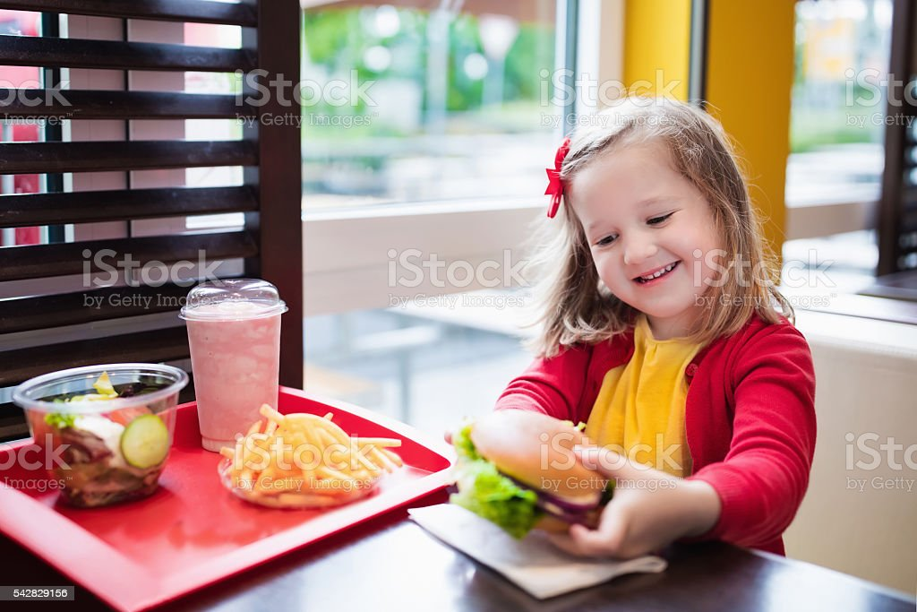 Happy little girl eating a hamburger in fast food restaurant stock photo