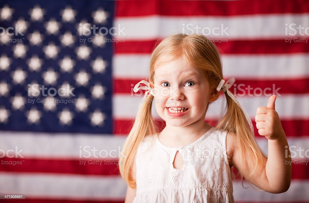 Happy Little Girl Giving Thumbs Up with American Flag royalty-free stock photo